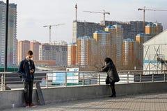 Люди на предпосылке домов под конструкцией в Москве Стоковые Фото