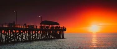 Люди на пристани на заходе солнца Стоковая Фотография
