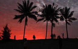 Люди на пляже во время захода солнца Стоковые Изображения RF