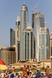 Люди на пляже перед жилыми небоскребами и гостиницами на Марине Дубай принятой 21-ого марта 2013 внутри Стоковые Изображения