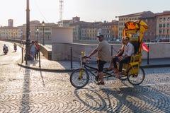 Люди на рикше цикла ехать над мостом Арно в Пизе, Италии Стоковое Изображение RF