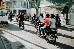 Люди на улице едут мотоциклы в городе мужчины, столице Мальдивов Стоковое Изображение