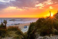 Люди на французском пляже на заходе солнца стоковая фотография
