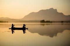 Люди на шлюпке в озере Стоковая Фотография
