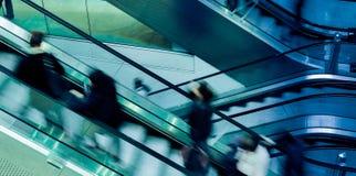 Люди на эскалаторах скрещивания стоковая фотография