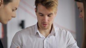 Люди обсуждают работать детали в офисе во времени дня акции видеоматериалы