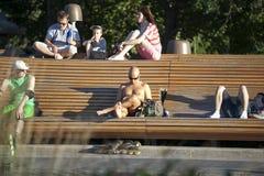 Люди ослабляют на длинном стенде в парке Стоковая Фотография