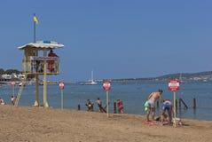 Люди отпускников игнорируют предупредительные знаки которое говорит предупреждение! Отсутствие заплывания! Опасность для жизни Стоковая Фотография