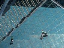 Люди очищая стеклянное здание стоковые изображения