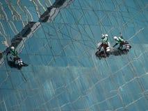 Люди очищая стеклянное здание стоковые фото