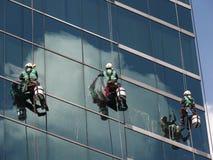 Люди очищая стеклянное здание стоковые изображения rf