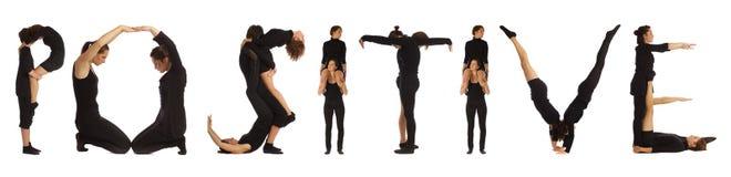 Люди одетые чернотой формируя ПОЛОЖИТЕЛЬНОЕ слово стоковое фото