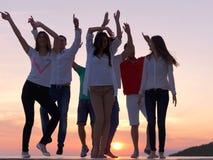 Люди партии на заходе солнца стоковое фото rf