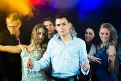 Люди партии танцуя в клубе диско Стоковая Фотография
