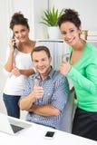 Люди показывая большие пальцы руки вверх в офисе стоковая фотография
