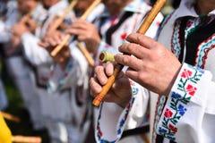 Люди поя на традиционных деревянных каннелюрах Стоковая Фотография