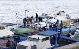Люди принимают вне поглощенную шлюпку от замороженного Дуная Стоковые Изображения