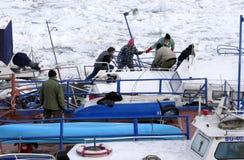 Люди принимают вне поглощенную шлюпку от замороженного Дуная Стоковое Изображение
