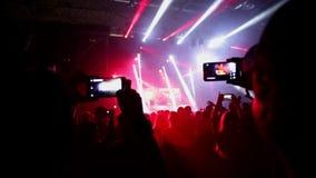 Люди принимая фото или записывая видео с их умными телефонами на концерте музыки акции видеоматериалы