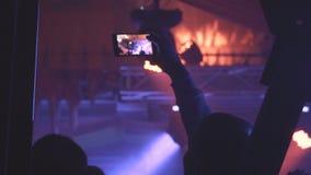 Люди принимая фото или записывая видео с их умными телефонами на концерте музыки видеоматериал