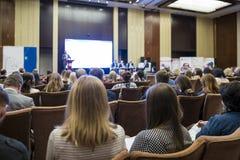 Люди присутствуя на бизнес-конференции сидя перед хозяином стоковые фотографии rf