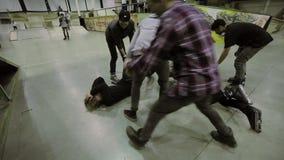 Люди приходят к мальчикам лежат на поле после трудного столкновения в парке конька Конькобежцы ролика ушиб удар сток-видео
