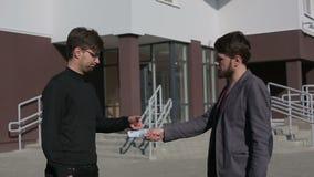 Люди проходят банкноты евро денег одина другого и трясут руки движение медленное акции видеоматериалы