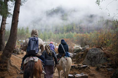 Люди путешествуя к Taktshang Goemba лошадью Стоковое Фото