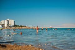 Люди плавая на воду в мертвом море Стоковые Изображения
