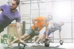 Люди работая с kettlebells в спортзале crossfit Стоковые Изображения