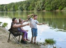 Люди располагаясь лагерем и удя, active семьи в природе, рыбе зацепляли приманка, река и лес, сезон лета стоковое фото rf
