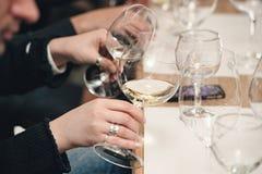 Люди рассматривают цвет вина и попытки как они пахнут в различных стеклах Стоковые Фото