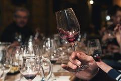 Люди рассматривают цвет вина и попытки как они пахнут в различных стеклах Стоковая Фотография RF
