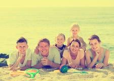 Люди семьи из шести человек лежа совместно на пляже Стоковое Изображение RF