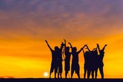Люди силуэта на заходе солнца Стоковая Фотография