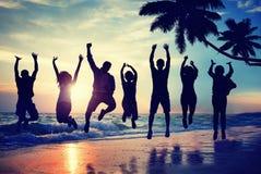 Люди силуэта скача с ободрением на пляже Стоковое фото RF