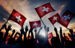 Люди силуэтов держа концепцию Швейцарии флага Стоковое фото RF