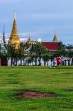 Люди сидят в Sanam Luang в фронте Wat Phra Kaew и грандиозного дворца Стоковая Фотография RF