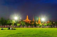Люди сидят в Sanam Luang в фронте Wat Phra Kaew и грандиозного дворца Стоковое Изображение RF