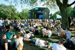 Люди сидят на траве и имеют остатки на внешней партии музыкального фестиваля Стоковое Изображение