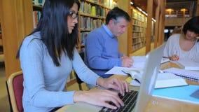 Люди сидя на библиотеке и делая их назначения видеоматериал