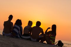 Люди сидя на пляже смотря заход солнца Стоковая Фотография