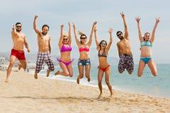 Люди скача на пляж Стоковая Фотография