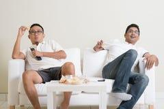 Люди смотря спичку в реальном маштабе времени спорта на ТВ дома Стоковое фото RF