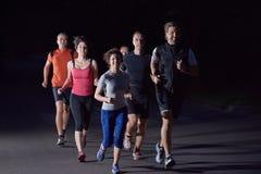Люди собирают jogging на ноче стоковые фотографии rf