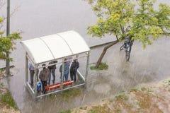 Люди стоя на автобусной остановке Стоковые Фото