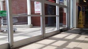 Люди с магазинной тележкаой идя через двери