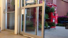 Люди с магазинной тележкаой идя через двери superstore видеоматериал