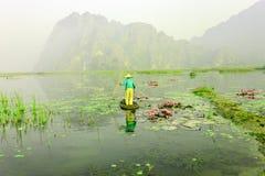 Люди с маленькой лодкой на Van Длинн pond, провинция Ninh Binh, Вьетнам стоковое изображение