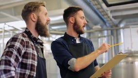 Люди с доской сзажимом для бумаги на винзаводе или заводе пива сток-видео